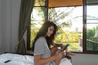 Young Girl On Bed Tropical Hotel Room Interior, Woman Using Cell Smart Phone Tropic Holiday Vacation Green Forest View
