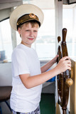 Boy holding the steering wheel of the ship - 138594474