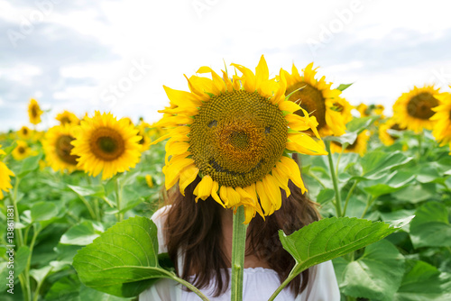 girl is hiding behind a sunflower in a field