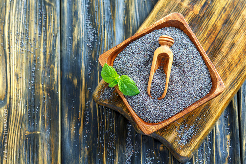 Square wooden bowl with poppy seeds.