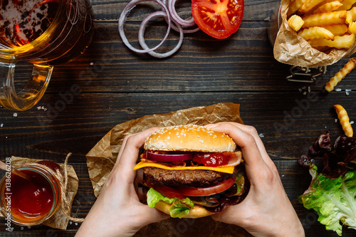 Hands holding fresh delicious burgers with french fries, sauce and beer on the wooden table top view