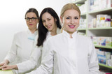 Professional female pharmacists portrait next to shelves