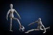 Two wooden figurines playing soccer concept on dark background with blue spotlight