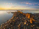 Baltic sea at beautiful sunrise,wooden breakwater in the light of the setting sun