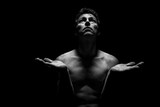 Low key portrait of shirtless man in Yoga position. Black background, monochrome picture.