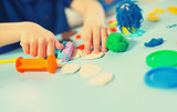 Child moulds from plasticine on table. Hands with plasticine.