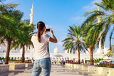 Young tourist woman shooting on mobile phone Sheikh Zayed great white mosque in Abu Dhabi, United Arab Emirates, Persian gulf. UAE is famous tourism destination