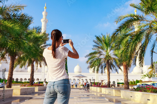 Foto op Aluminium Abu Dhabi Young tourist woman shooting on mobile phone Sheikh Zayed great white mosque in Abu Dhabi, United Arab Emirates, Persian gulf. UAE is famous tourism destination