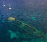 Bird view on the ship wreck in croatian sea with snorkeling people and two boats anchoring in background.