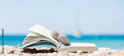 Reading in summer vacation, concept. Book on the pebble beach. - 138693417