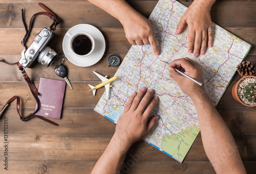 Foto Murales Young couple planning  vacation trip with map. Top view.