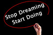 Hand Writing Stop Dreaming Start Doing with a marker over transparent board.
