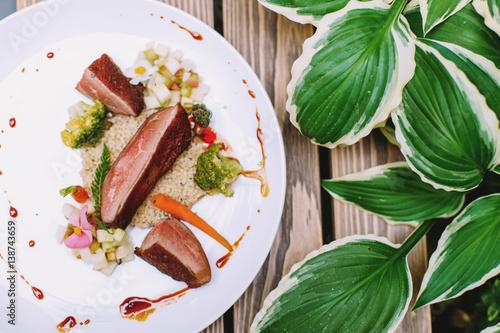 Wykwintne danie na talerzu obok rośliny