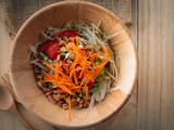 Traditional Thai food papaya salad with shrimp on top able plan on wooden background wallpaper