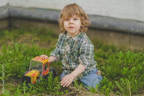 Poster Маленький мальчик кудрявый с машинкой с игрушкой на траве в рубашке