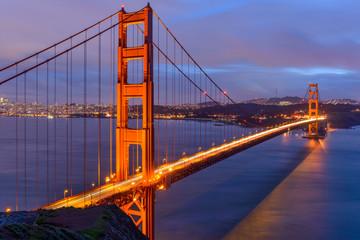 Sunset Golden Gate Bridge - A cloudy-winter-day sunset view of Golden Gate Bridge, looking from Hilltop at Marin Headlands toward San Francisco Peninsula at south. San Francisco, California, USA.