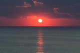 Sunset / sunrise over ocean / sea horizon with clouds.