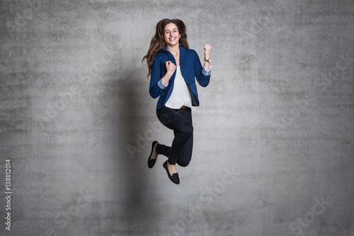 Fototapeta euphoric business woman jump wall