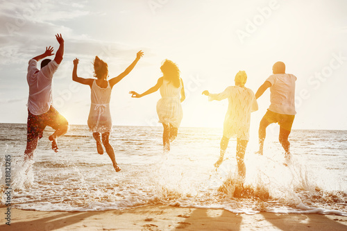 Happy friends group people sunset sea