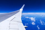 Aerial view of airplane wing over blue sky