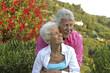 Leinwanddruck Bild - Glueckliches Senioren Paar im Garten ihres Ferienhauses