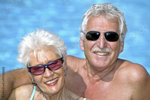 Leinwanddruck Bild Glueckliches Senioren Paar im Urlaub am Pool