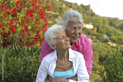 Leinwanddruck Bild Glueckliches Senioren Paar im Garten ihres Ferienhauses