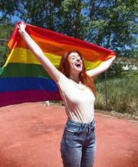 Mujer gritando mientras sujeta una bandera arco iris