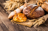 Assortment of baked bread on wooden table background - 138875645