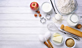 Baking ingredients: flour, eggs, milk, butter, brown sugar, cinnamon, nuts, yogurt, walnut and apple with eggbeater, cake pans and rolling pin - 138884849