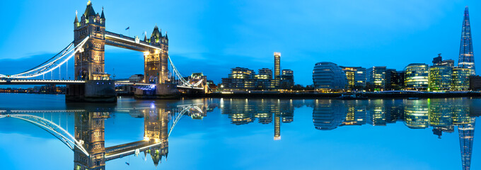 Panorama of Tower Bridge with blue sky and reflection in London. England