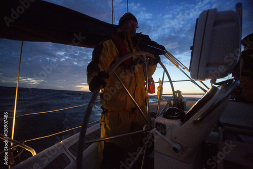 Keuken foto achterwand Schip Man Steering Wheel On Yacht During Sunset
