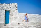 Fototapety Cute girl in blue dress having fun outdoors near Paraportiani church.