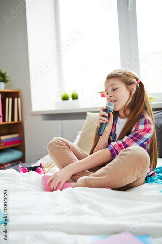 Póster Ginger-haired school girl with ponytails sitting on her bed and singing into mic