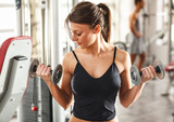 Young female with sport body doing workout at the gym.She lifting dumbbells.