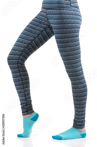 Poster Close up view of woman legs in colourful striped thermal pants and blue socks fr