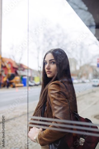Poster Beautiful brunette woman standing at bus station and waiting for city bus