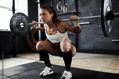 Poster Intense crossfit workout in dark gym: strained young sportswoman performing shou