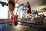 Low-angle view of gym clients warming up on treadmill before hard workout