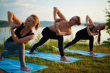 Instructor and two young women doing yoga twists on river bank in summer evening