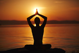 Silhouette of man meditating in lotus pose with his hands lifted above head in namaste and enjoying gorgeous sunset