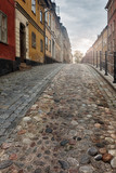 Old picturesque cobblestone street in Stockholm in early morning light.