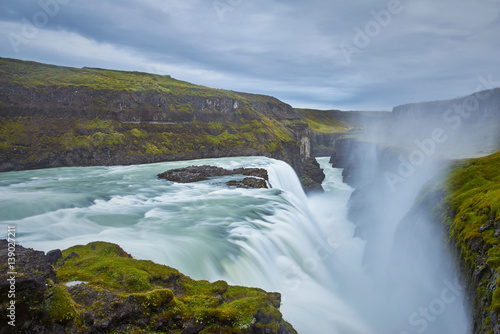 Fototapeta Cloudy sunrise at Gulfoss Iceland with flowing waterfall and big splash of water