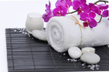 Spa setting with candle, towel ,orchid, on mat