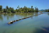 Traditional Polynesian old fish trap made with stones in a channel between a lake and the ocean, Huahine island, French Polynesia, South Pacific