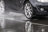 Sports car driven on rainy roads close up on a wheel with motion blur effect - 139081293