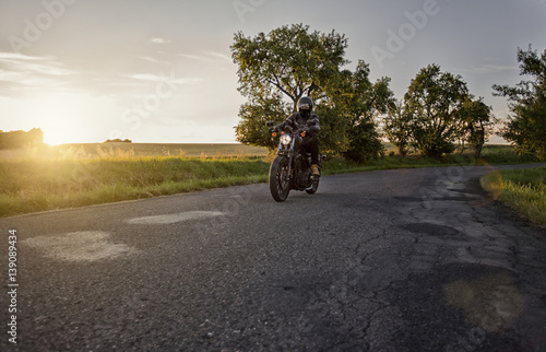 Poster Chopper rider, biker, driving on a road during beautiful sunset