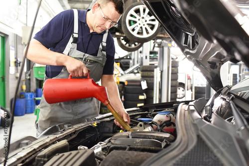 fototapeta na ścianę Kundendienst Ölwechsel am KFZ - Mechaniker in einer Autowerkstatt // Customer service Oil change