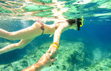Snorkel couple swimming together in tropical sea with follow me composition - Snorkeling tour in exotic diving scenarios - Fun travel concept with active girl underwater - Soft focus due water density - 139107225