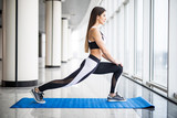Fototapety Stretching. Young beautiful young woman in sportswear doing stretching while standing in front of window at gym